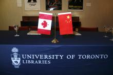 Photo of Canadia and Chinese flags on desk.